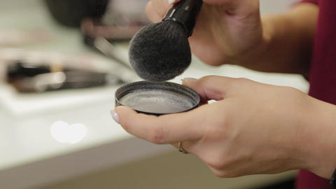 Professional makeup artist brushes powder with a brush Live Action