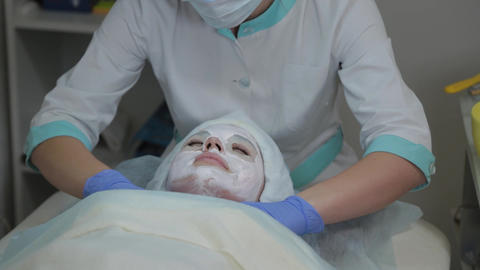 Professional cosmetologist woman removes mask from client's face with wet wipes Live Action