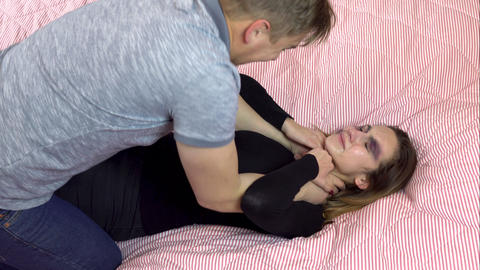 Young man strangling a young woman on the bed. A woman with bruises on her face Live Action