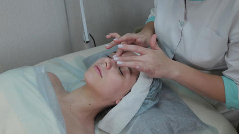 Professional beautician woman performs facial massage to client woman Live Action