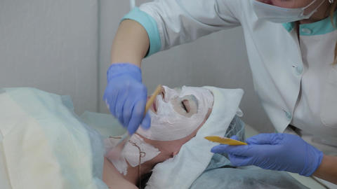Professional beautician woman applying mask to client with face brush Live Action
