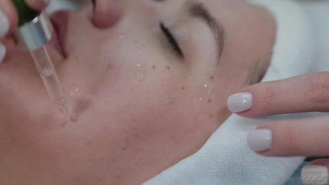 Professional beautician woman applying oil to skin on a wedge with a pipette Live Action