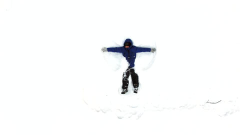 Happy smiling boy lying in the snow, moving his arms and legs and making a snow Live Action