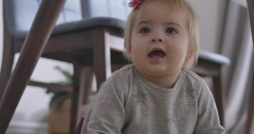 Portrait of charming Caucasian baby girl with grey eyes and blond hair looking Live Action
