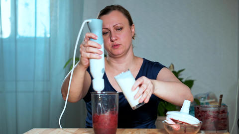 The concept of healthy eating. Close-up of a woman mixing fruit and berry puree Live Action