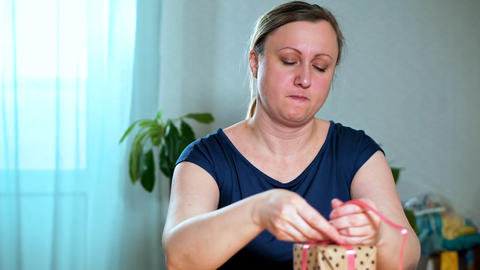 A middle-aged woman packs a gift Live Action
