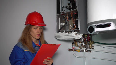 Female technician make maintenance of heating boiler in private house Live Action