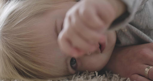 Close-up portrait of extremely beautiful Caucasian baby girl lying on bed Live Action