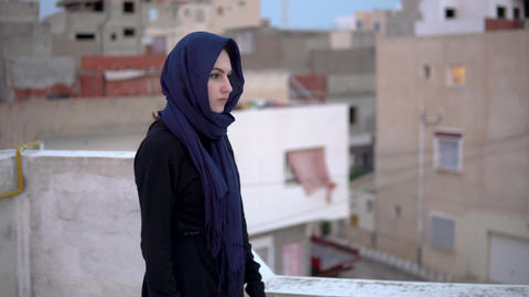 Young woman in the Arab headscarf. A woman is walking on the roof. On the roof Live Action