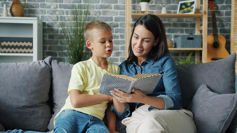 Young lady reading fairy-tale to cute boy educating child at home indoors Live Action