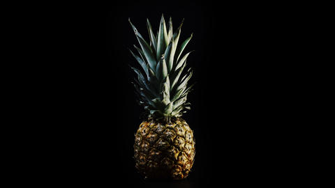 Exotic pineapple against black background Live Action