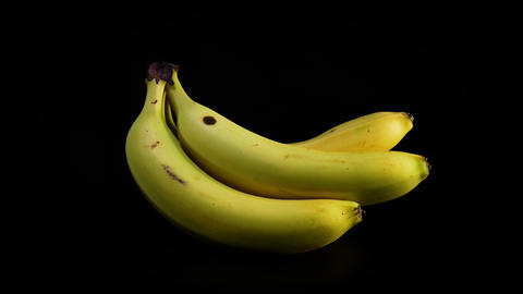 A bunch of yellow bananas slowly rotating against black background Live Action
