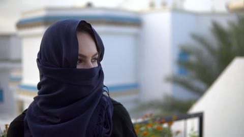 Young woman in arabic burqa. A woman is looking at the camera. Against the Live Action