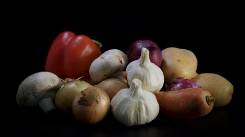 Mixed fresh organic vegetables rotate against black background Live Action