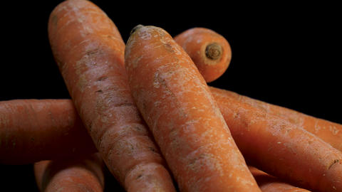 Fresh organic carrots in close up rotate against black background Live Action