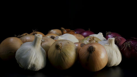 Mixed organic Onions rotating against black background Live Action