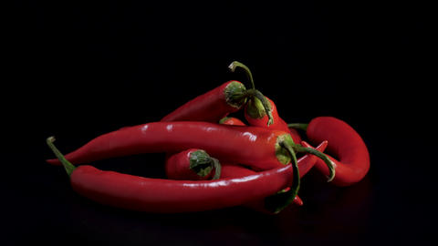 Fresh red hot chili pepper rotating against black background in studio Live Action