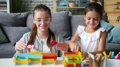 Happy mother and daughter playing with construction blocks indoors at home Live Action