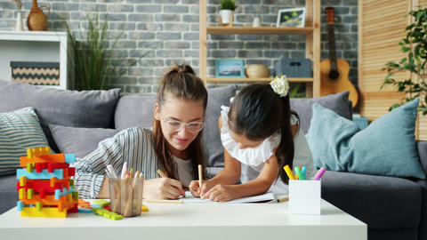 Happy little girl drawing at home with caring mother using pencils having fun Live Action