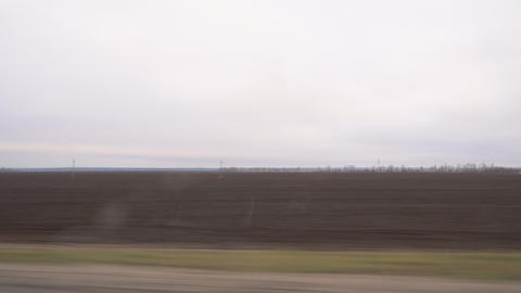 View of a plowed field from the window of a car Live Action
