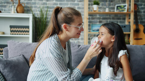 Loving mother putting lip gloss on little daughter's lips smiling talking at Live Action