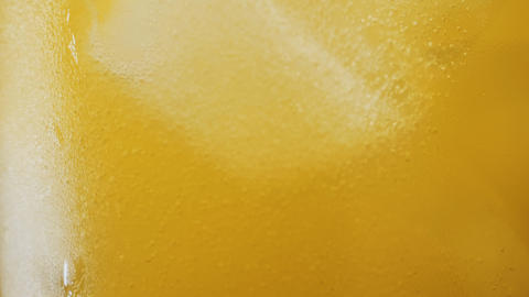 Macro shot in slow motion of Orange soda and ice in a glass background Live Action