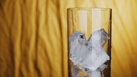 Slow motion shot of a glass filled up with ice cubes shot in studio with yellow background Live Action