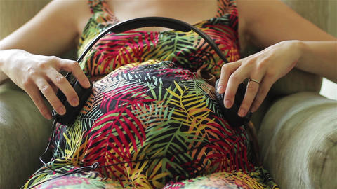 Pregnant Woman with Headphones on her Belly Sitting on Sofa at Home Acción en vivo