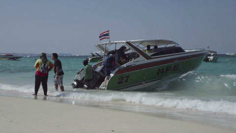 Tourists getting into a boat on the beach Footage