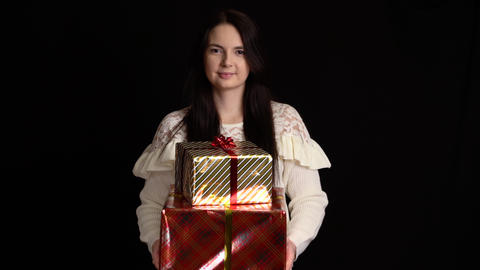 Young woman gives a gift box on black background. gift box with white ribbon for Live Action