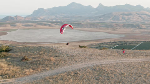 A man on a paraglider comes off the ground and flies to the sea against a Live Action