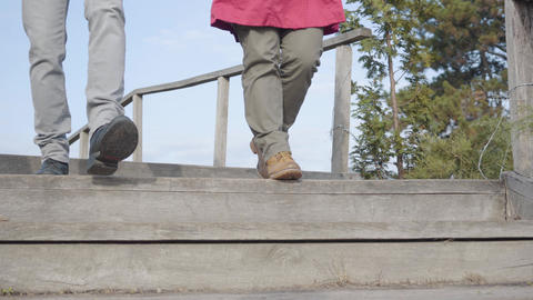 Camera following man's and woman's legs walking down the stairs outdoors. Young Live Action