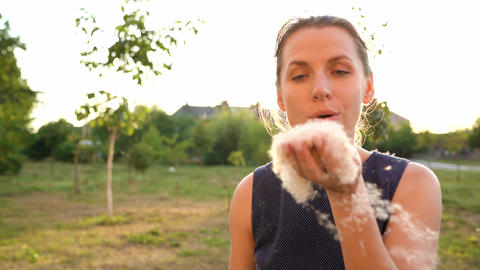 Woman blows on reeds outdoors in sunny day. Fluff from reeds flies around. Slow Live Action