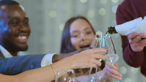 Slow motion a man pours champagne to friends. The multiethnic company celebrates Live Action