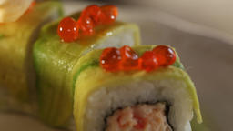 Close-up of sushi rolls decorated with avocado slices.The process of decorating rolls with red Live Action