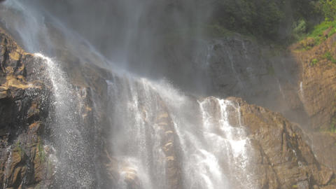 waterfall by wet stones appears from behind brown rock ライブ動画