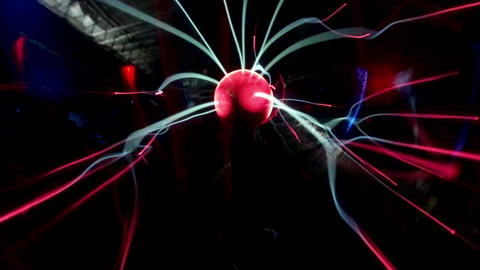 Lasers moving red plasma ball against black background Live Action