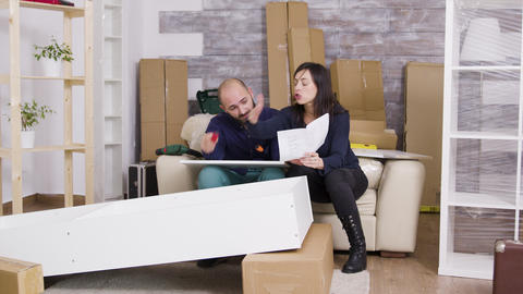 Caucasian couple arguing while assembling a shelf Live Action
