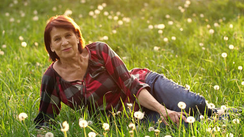 Happy elderly woman lying on the grass Live Action