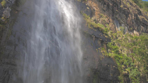 water falls from high brown rocky cliff with green trees Live Action