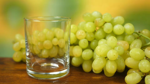 Juice Pours Into Glass with Organic White Grapes on Table Live Action