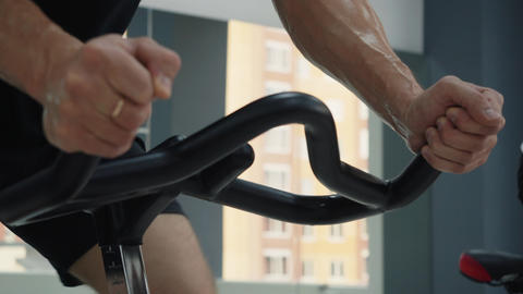 Male sweating hands holding handle indoor bike on cycling class. Wet male hands Live Action