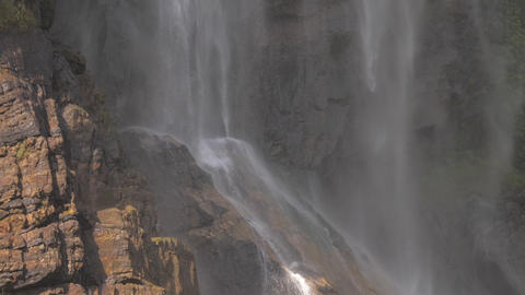 wonderful large waterfall streams fall on brown rocky cliff Live Action