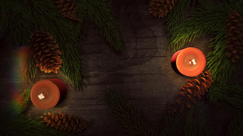 Animated close up Christmas candle and green tree branches on wood background 애니메이션