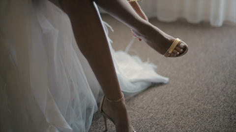 Bride wears her wedding shoes. Wedding morning. Close-up elegant woman's sandals Live Action