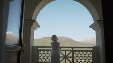 A girl in a white robe stands on the balcony and enjoys. sexy girl in white robe Live Action