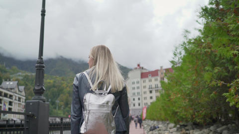 A young girl walks in Sochi on Rosa Khutor. Young tourist walks with a backpack Live Action