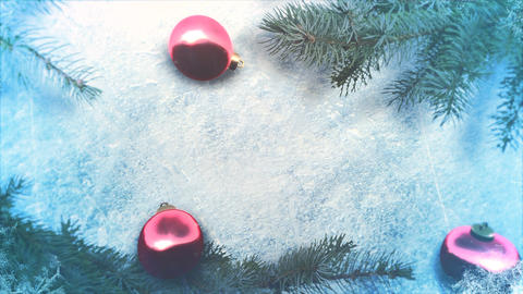Animated close up red balls and Christmas green tree branches on shiny ice background 애니메이션