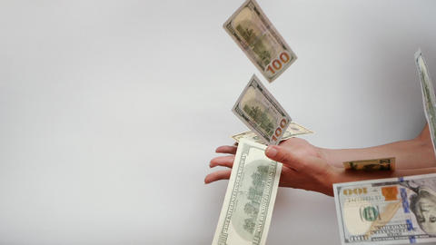 Woman's hands try to catch falling US Dollar banknotes falling in slow motion Live Action