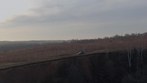 Suv car driving along cliff edge on background yellow field and bare autumn trees. Off road car Live Action